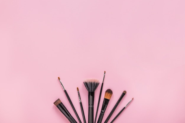Different powder brushes on pink table Free Photo