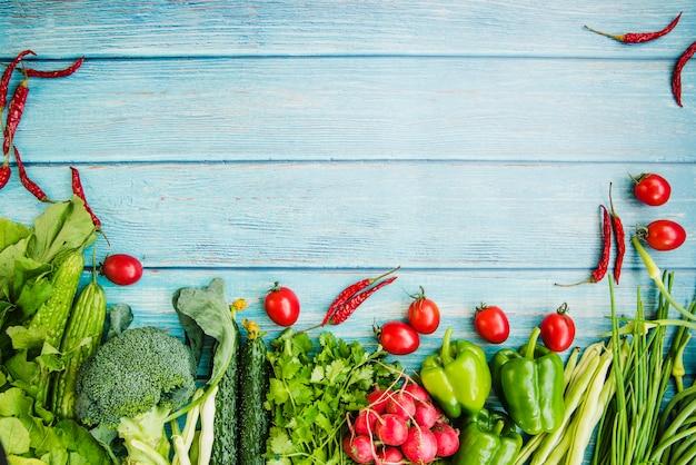 Различные сырые овощи на синем деревянном столе Premium Фотографии