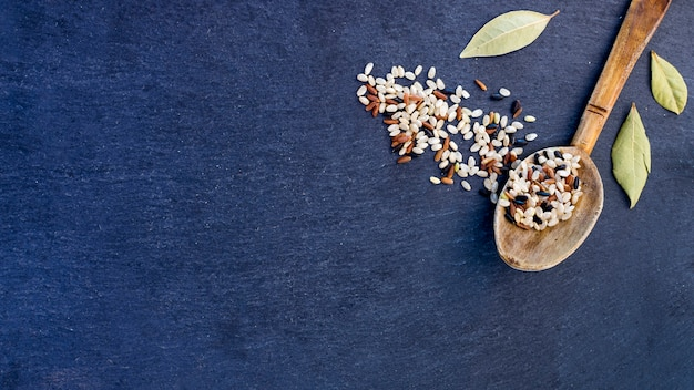 Different rice grains in wooden spoon on blue table Free Photo