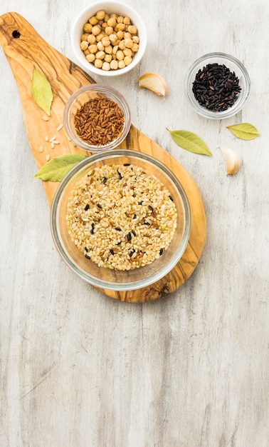 Different rice types in bowls on wooden board Free Photo
