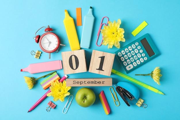 Различные школьные принадлежности и деревянный календарь на синем Premium Фотографии