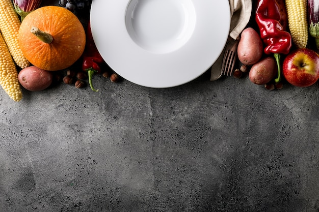 Different seasonal autumn vegetables and fruits with empty plate on grey background Free Photo