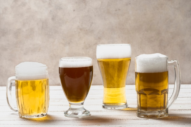 Different shape of glasses with beer on table Free Photo