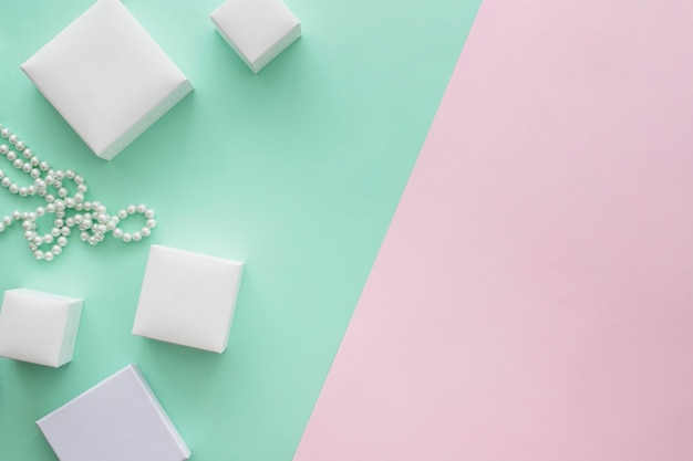 Different size of boxes and pearl necklace on colored background Free Photo