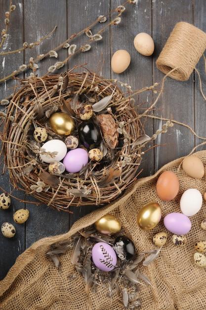イースターのための異なるサイズの塗装色の卵と羽。自由ho放に生きるスタイル。 Premium写真