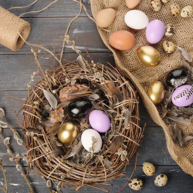 イースターのための異なるサイズの塗装色の卵と羽 Premium写真