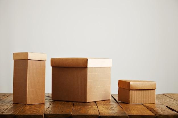白い壁のあるスタジオの木製テーブルにあるさまざまなサイズと形のベージュの紙箱 無料写真