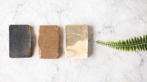 Different soaps for skincare next to green leaf Free Photo