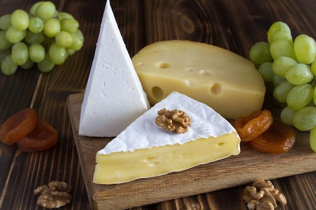 さまざまな種類のチーズ、ブドウ、茶色のまな板にドライアプリコット Premium写真