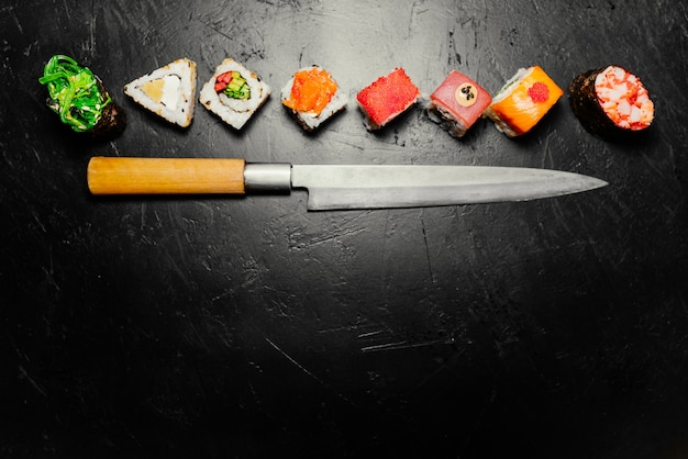 Different sushi with japanese knife on black stone slate background. sushi on a table. Free Photo