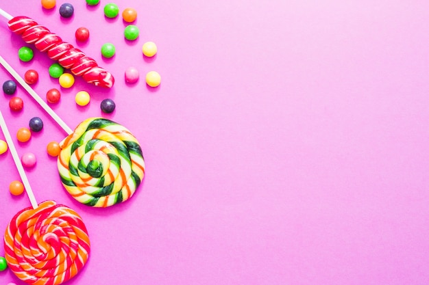 different sweet candies on pink background photo free