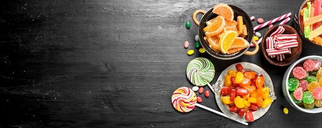 다른 달콤한 사탕, 젤리와 설탕에 절인 그릇에. 검은 칠판에. 프리미엄 사진