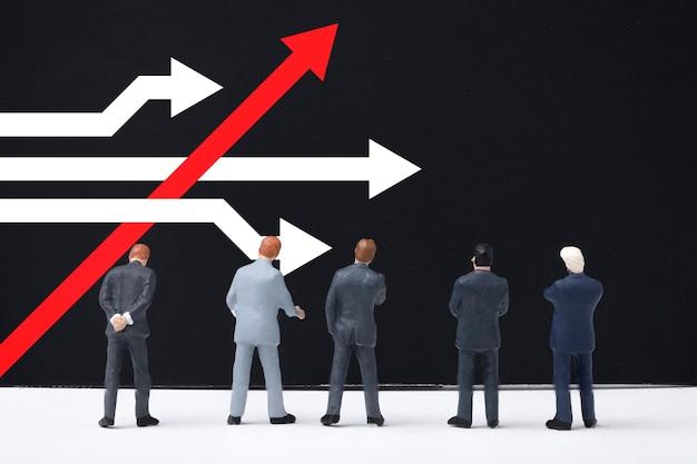 Различное мышление и концепция разрушения бизнеса и технологий. бизнесмен стоит и рассматривает красную стрелку с белой стрелкой на доске. Premium Фотографии