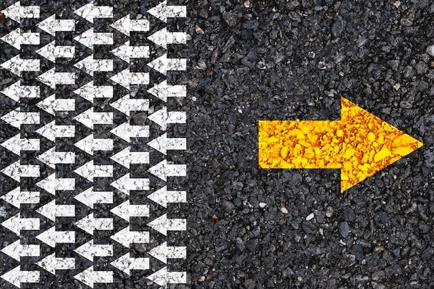 Различное мышление и концепция разрушения бизнеса и технологий. желтая стрелка противоположного направления с белой стрелкой на дорожном асфальте. Premium Фотографии