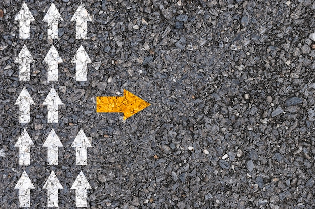 Различное мышление и концепция разрушения бизнеса и технологий. желтая стрелка вне направления линии с белой стрелкой на дорожном асфальте. Premium Фотографии