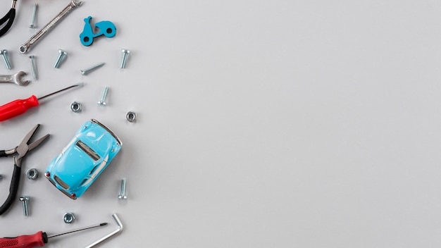 Different tools with toy car on grey table Free Photo