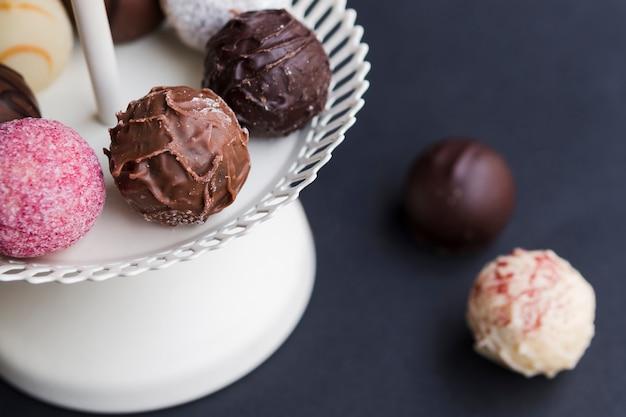 Different truffles on white dessert dish Free Photo