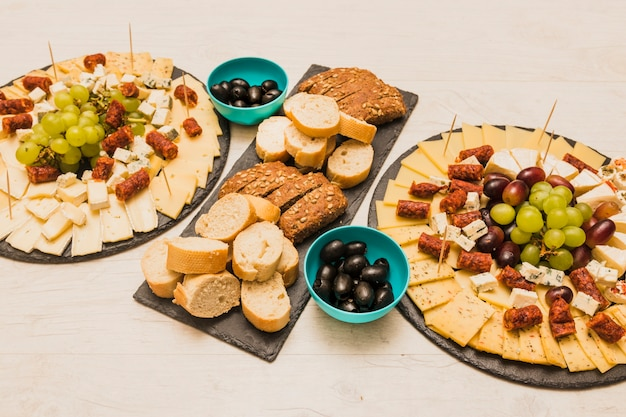 Different type of bread slices with olives and platter cheese on wooden desk Free Photo