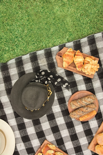 Different type of breads with hat on blanket over the green grass Free Photo