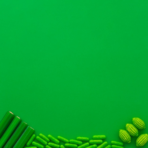 Different type of candies at the bottom of green background Free Photo