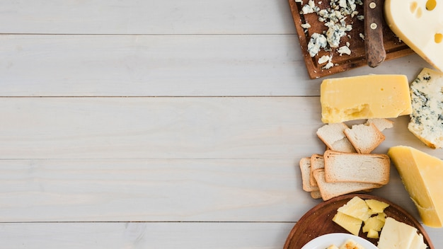 Different type of cheese with bread on wooden table Free Photo