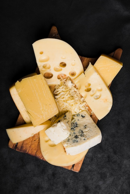 Different type of cheese on wooden board over the black background Free Photo