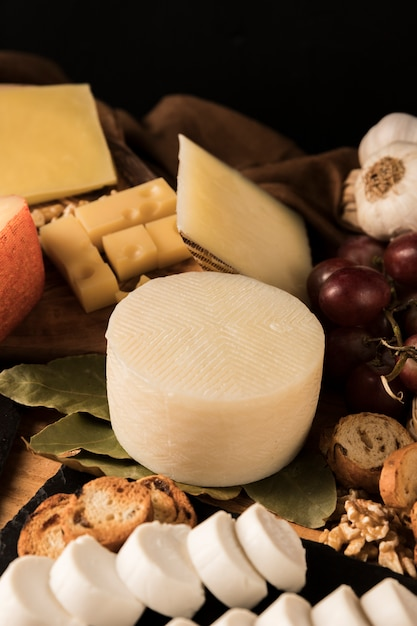 Different type of cheeses and ingredient on table Free Photo