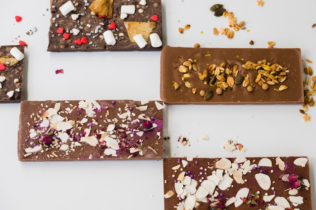 Different type of chocolate bars on white backdrop Free Photo