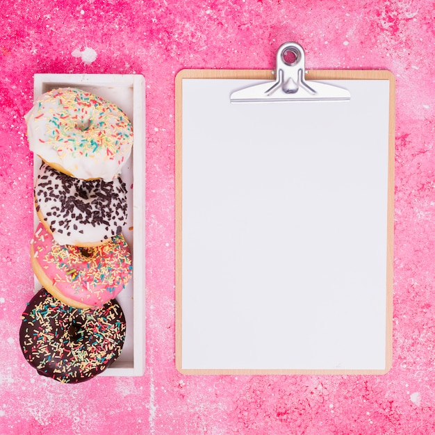 Different type of donuts in white rectangular box near the clipboard with white paper against pink background Free Photo