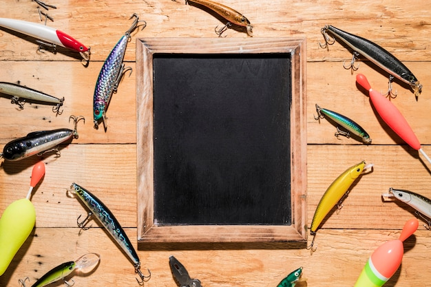 Different type of fishing lures around the black wooden slate on wooden backdrop Free Photo
