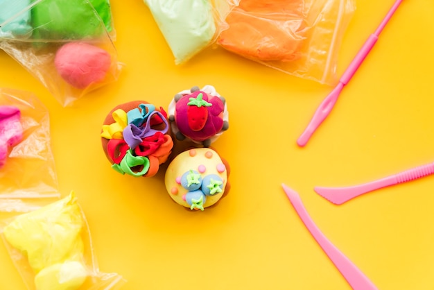 Different type of handmade colorful clay on yellow backdrop Free Photo