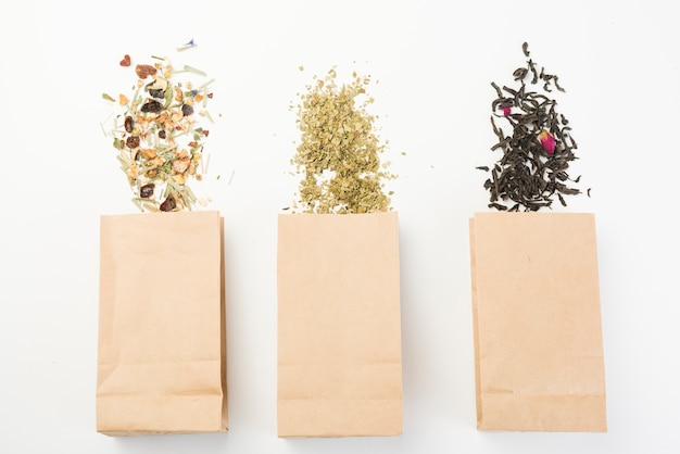 Different type of herbal tea spilling from brown paper bag on white background Free Photo
