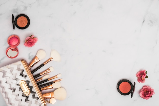 Different type of makeup brushes in the bag with compact face powder and rose flowers on white backdrop Free Photo