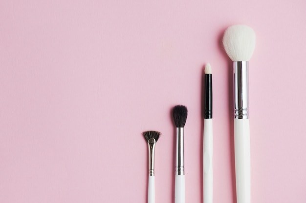 Different type of makeup brushes in a row on pink background Free Photo