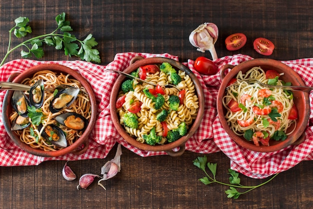 Different type of pasta on tablecloth over the wooden table Free Photo