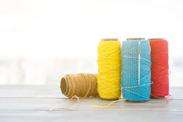 Different type of spool yarn with needle on wooden desk Free Photo