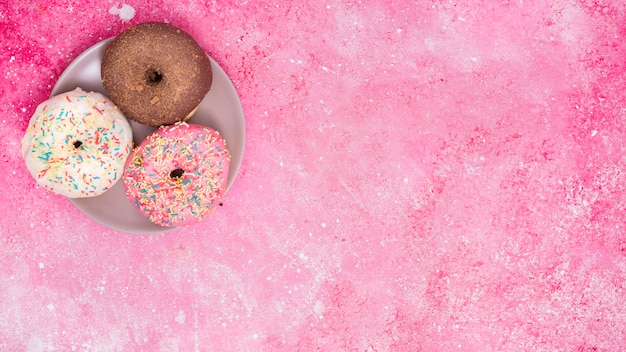 Different type of three donuts on stainless steel against pink background Free Photo