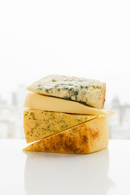 Different type of triangular cheese wedges with herbs on white desk Free Photo