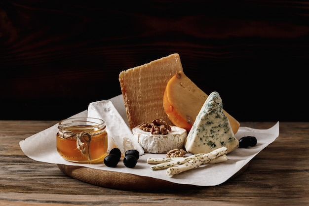 Different types of cheeses. slices of cheese brie or camembert with parmesan, cheddar ,blue cheese , and other with nut and honey on wooden board on dark background Premium Photo