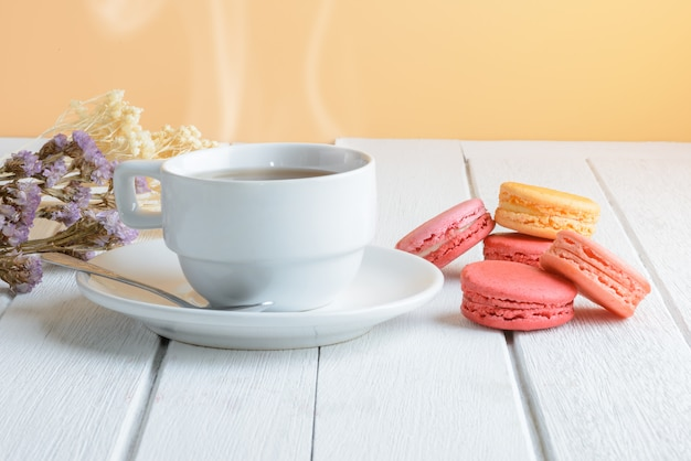 Different types color of macaroons with cup of hot tea on white wooden surface Premium Photo