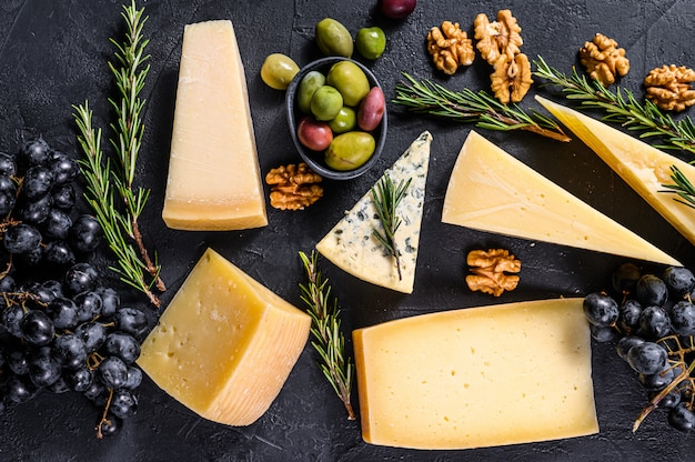 Different types of delicious cheese, walnuts and grapes. top view Premium Photo