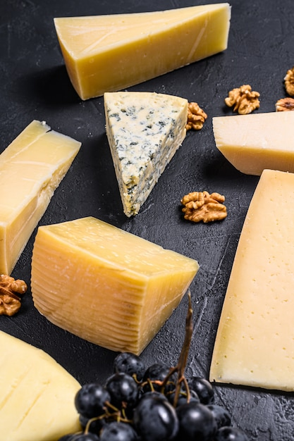 Different types of delicious cheese with walnuts and grapes. top view Premium Photo