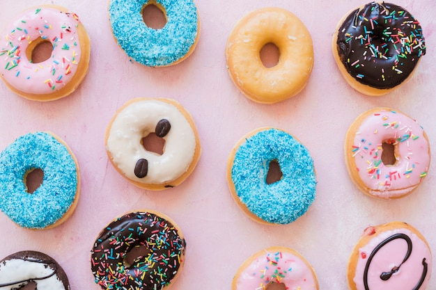 Different types of donuts in a row on pink backdrop Free Photo