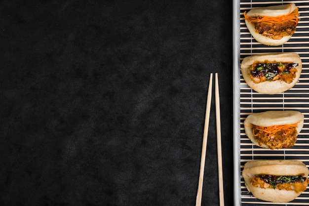 Different types of gua bao on placemat with chopsticks against black textured backdrop Free Photo