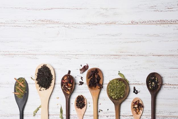 Tipi differenti di erbe sui cucchiai di legno sopra lo scrittorio bianco Foto Gratuite