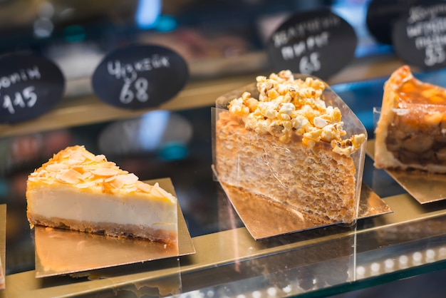 Different types of pastries in the glass cabinet with price tag Free Photo