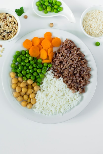 Different types of porridge with vegetables on big plate with rice bowls Free Photo