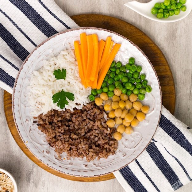 Different types of porridge with vegetables on big wooden board Free Photo