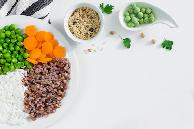 Different types of porridge with vegetables on white plate Free Photo