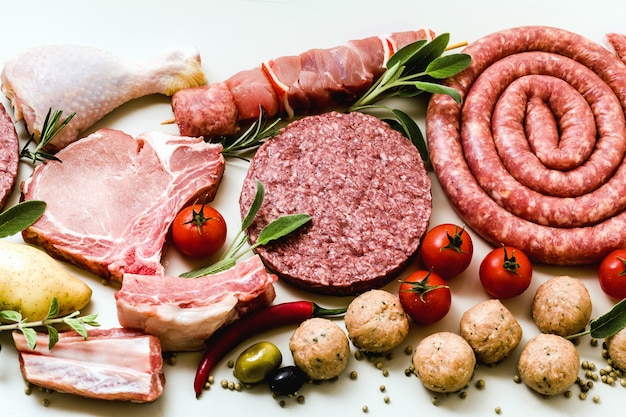 Different types of raw meat: chicken thighs, pork and beef burgers, ribs and kebabs, turkey meatballs, ready to be cooked with potatoes, hot pepper, olives and black olives and aromatic herbs Premium Photo